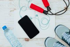 Sunda och aktiva livsstilar begrepp, hopprep, hantlar, sportskor, flaska för kondition, av vatten, smartphone med headphonen Arkivbild