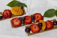 Sunda och smakliga rostade bröd med ostmassaost, frukter och bär på ett vitt pergamentpapper royaltyfria foton
