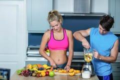 Sunda par som förbereder en smoothie Arkivbild