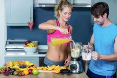 Sunda par som förbereder en smoothie Fotografering för Bildbyråer