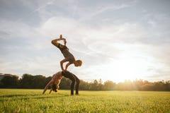 Sunda par som gör acroyoga på gräs Arkivfoton