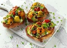 Sunda rostade bröd med bakade söta körsbärsröda tomater och grillade zucchininband duggade med balsamic vinäger Royaltyfria Bilder
