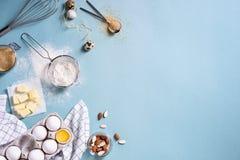 Sunda stekheta ingredienser - pudra, mandelmuttrar, smör, ägg, kex över en blå tabellbakgrund Bageribakgrundsram överkant