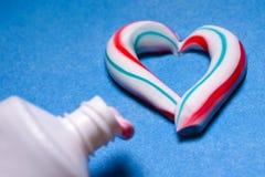sunda tänder Hygien av det muntliga hålet Kulör tandkräm från ett rör Pasta i form av en hjärta royaltyfri fotografi