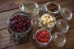 Sunda torkade frukter, frö och muttrar på trätabellbakgrund Arkivfoto