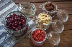 Sunda torkade frukter, frö och muttrar på trätabellbakgrund Fotografering för Bildbyråer