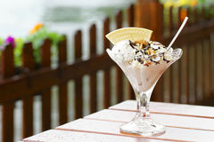Sundae. Ice cream with chocolate and nuts on the table in the rainy weather with the background of the river Stock Photos