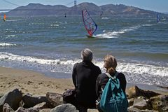 Sunday Afternoon. A couple watching the windsurfers in the San Francisco Bay with the Golden Gate Bridge in the far distance Royalty Free Stock Photography