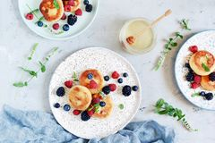 Sunday breakfast with cheesecake, honey, fresh berries and mint. Cottage cheese pancakes. Or curd fritters decorated honey and berries in plate on blue table stock photography