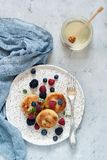 Sunday breakfast with cheesecake, honey, fresh berries and mint. Cottage cheese pancakes. Or curd fritters decorated honey and berries in plate on blue table royalty free stock image
