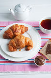 Sunday breakfast. Croissants with tea and peanut butter. Royalty Free Stock Photo