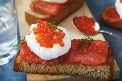Sunday breakfast with poached egg, caviar and red fish. Closeup Stock Images