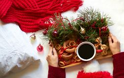 Sunday christmas morning breakfast in bed: female hands put a tray with decoration and treats: a cup of coffee and bagels for dess. Ert, top view from above stock photo