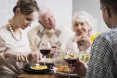 Sunday dinner with happy family. Mature couple and young marriage sitting beside table during family dinner Royalty Free Stock Photo