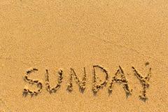 Sunday - inscription by hand on a beach sand. Royalty Free Stock Photography