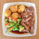 Sunday Lunch. Meal of roast lamb, roast potatoes, gravy and vegatables on a white plate from above Royalty Free Stock Photo