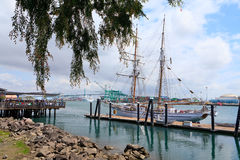 Sunday morning in the port of Los Angeles. Two-masted sailing ship in the port of Los Angeles, the bridge and cruise ship in the background Stock Image