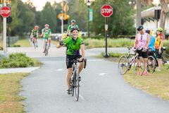 Man waves to camera as he approaches on bike, editorial. royalty free stock photo