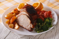 Sunday Roast: pork with vegetables and Yorkshire pudding closeup Royalty Free Stock Photography
