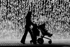 Sunday Stroll. A mother and her two kids take a stroll near a fountain in Lisbon, Portugal stock photography