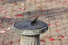 Sundial. Weathered brass sundial on pedestal base. patio background with scattered red leaves provides copy space Stock Photo