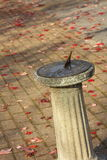 Sundial. Weathered brass sundial on pedestal base. patio background with scattered red leaves provides copy space Royalty Free Stock Images