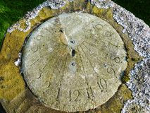 Sundial covered with lichen in graveyard Royalty Free Stock Photography