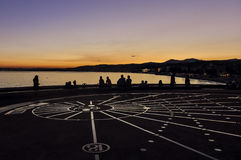 Sundial in Nice, France: French Riviera. Sundial in Nice, France at sunset on Promenade des Anglais with outline of people. A famous place in French Riviera Stock Photography