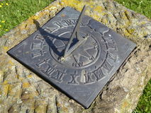 Metal sundial on stone plinth. An old metal sundial in a churchyard in England Stock Images