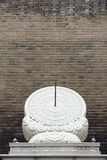 Sundial. The stone sundial is placed in front of the brick wall. Sundial was Chinese ancient timing tool Stock Photos
