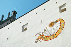 Sundial on white castle wall at sunny day Stock Images