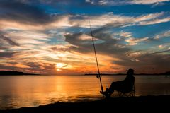 Sundown Fishing. Made sitting by his fishing rod at sunset Royalty Free Stock Images