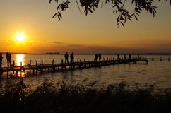 Sundown in the lake with people Royalty Free Stock Photography