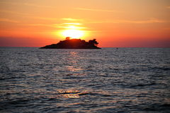 Sundown on ocean with island Royalty Free Stock Images