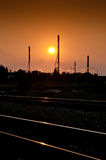 Sundown over the factory. Smoggy sundown in industrial area with noticeable smog and air pollution. Railway tracks and a factory are the main subjects Royalty Free Stock Images
