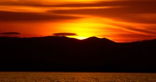 Sundown. A Picture of a beautiful sundown over mountains and  a sunset sea,in a day afternoon of February in a greek town thessaloniki Stock Photo