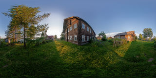 Sundown in russian rustic village. Summer view of traditional rustic russian village with wooden houses and birch tree. Sundown time high contrast scene. Full Royalty Free Stock Image