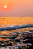 Sundown on seacoast. The sun sits down above the sea generating grief in heart Stock Images