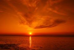 Sundown sun in sea Stock Images