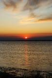 Sundown sun in sea Stock Photos