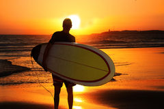 Sundown surfer. A young male surfer with a surfboard under his arm, coming out of the water by sundown royalty free stock image