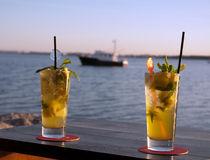 Sundowner cocktails with blurred boat. Colorful cocktail glasses for two with blurred boat in background Stock Photography