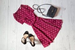 Sundress burgundy, black handbag and shoes on a wooden background. Fashionable concept Stock Image
