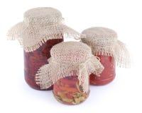 Sundried томаты, части красного и зеленого перца chili с соусом масла и chili в стеклянных банках с крышкой дерюги на верхнем iso Стоковые Изображения