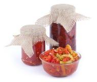 Sundried томаты, части красного и зеленого перца chili с соусом масла и chili в стеклянных банках и шарах с крышкой дерюги дальше Стоковое Изображение RF