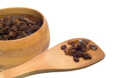 Sundried Raisins. A small cluster of sundried raisins being displayed on a wooden spatula with more in a bowl OOF in the background Royalty Free Stock Image