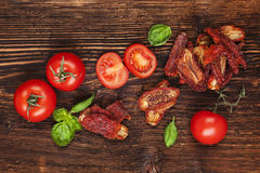 Sundried tomatoes. Delicious sundried, fresh tomatoes and basil herbs on brown wooden vintage textured background, top view. Traditional mediterranean kitchen Royalty Free Stock Photography