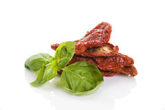Sundried tomatoes. Sundried tomato with fresh basil herbs on white background. Culinary italian eating Stock Photography