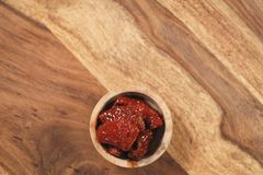 Sundried tomatoes in wood bowl on table Stock Image