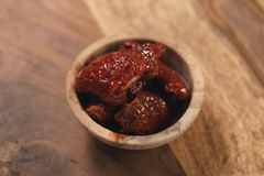 Sundried tomatoes in wood bowl on table Royalty Free Stock Photography